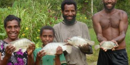 Papua New Guinean family holding fish